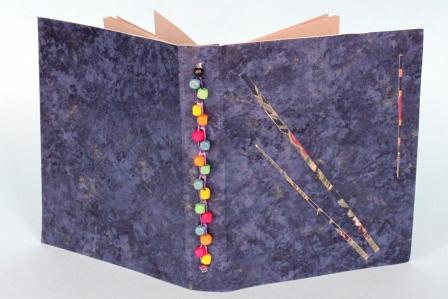 A book showing Rowan Rainwalker's beading using a Chain Stitch on the book spine