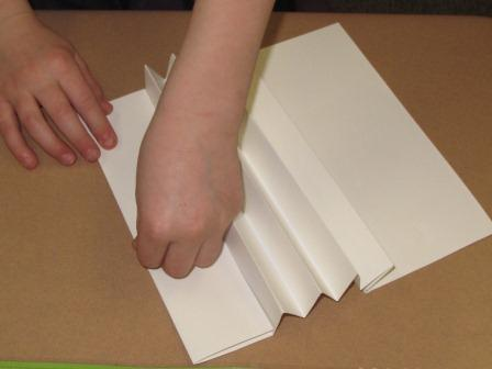 To make the fifth accordion, start by folding  just one edge over to meet the closest crease.