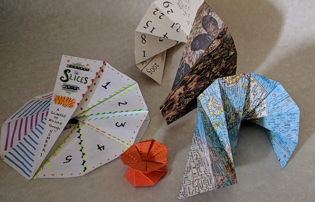 Spiraling pages made from copy paper, an old calendar, outdated map, and a pretty orange scrap