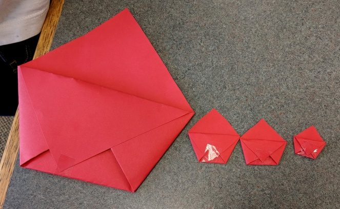 Spontaneous Scaling of Origami Pocket by First Grader. I see this happen frequently.